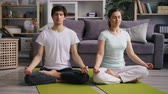 stillness : Young people attractive girl and guy relaxing in lotus pose with closed eyes after yoga practice sitting on floor on bright mats. Millennials and health concept. Stock Footage