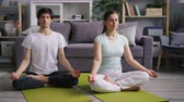 lotos : Husband and wife attractive young people are resting in lotus position meditating together at home sitting on floor with closed eyes. Zen and family concept. Wideo