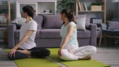 lotos : Girlfriend and boyfriend exercising at home then relaxing in lotus position siting on floor putting hands on knees resting enjoying peaceful atmosphere.