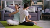lábtörlő : Happy young couple Caucasian woman and Asian man are doing yoga together bending body backwards in pairwork enjoying exercise. Youth and activity concept. Stock mozgókép