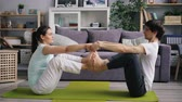 gleichgewicht : Man and woman happy couple are doing pair yoga at home holding hands joining feet sitting on floor in modern apartment. Family and active lifestyle concept.