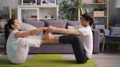 gleichgewicht : Sportive students are doing yoga for couples exercising in cozy apartment together enjoying activity and healthy lifestyle. Youth and relationship concept. Stock Footage