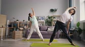 trabalhar fora : Cute married couple girl and guy are training at home doing yoga indoors standing on mats bending sidewards concentrated on exercise. People and apartment concept.