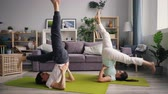 pies levantados : Man and woman are doing sequence of yoga asanas in inverted position practising at home training together. Active young people, relationship and sports concept.