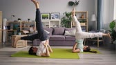 pies levantados : Sporty couple young man and woman are exercising at home doing yoga together practising inverted asanas then relaxing on mats on floor in nice apartment.