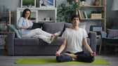 lotos : Asian guy husband is focused on meditation sitting on yoga mat in lotus position while wife is working with computer at home relaxing. Youth and relaxation concept. Wideo