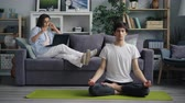 lotos : Young husband Asian guy is meditating in lotus position when girl freelancer is using laptop talking on mobile phone at home. Modern technology and yoga concept.