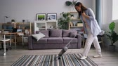 staubsauger : Pretty housewife is cleaning carpet with vacuum cleaner dancing laughing having fun enjoying housework in apartment. Modern technology, electrical appliances concept.