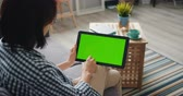 portátil : Person young woman is holding tablet touching green mock-up screen using modern device at home. Technology, electronic gadgets, house and youth concept. Stock Footage