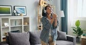 mikrofon : Happy young woman in headphones is singing in remote control dancing having fun in apartment. Joyful millennials, leisure time and funny activity concept.
