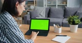 электроника : Slow motion of person young woman using laptop computer with green mock-up screen at home touching touchpad sitting at desk in apartment. Media and internet concept.