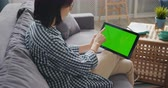 portátil : Young lady is touching green mock-up screen of modern tablet using gadget in apartment sitting on sofa enjoying media content. Youth and devices concept.