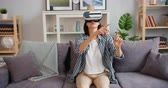 inovador : Young woman in vr glasses moving arms sitting on sofa in apartment enjoying new experience and modern technology. Youth, house and trendy gadgets concept.