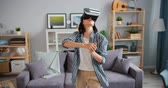 развлекать : Happy girl is playing game wearing virtual reality glasses in apartment alone having fun with new technology. Entertainment and modern gadgets concept. Стоковые видеозаписи