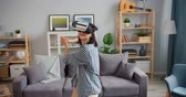развлекать : Happy person young woman is having fun with augmented reality glasses wearing headset at home enjoying activity. Youth, innovation and house concept.