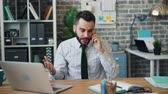 zařvat : Mad young man is yelling on mobile phone gesturing working in office alone sitting at desk discussing problem with business contact. People and work concept.