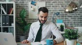 caderno : Happy manager bearded young man is communicating with laptop and wireless earphones looking at screen then writing in notebook smiling. People and gadgets concept. Stock Footage