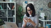 mass media : Beautiful woman in glasses is using smartphone touching screen smiling sitting at desk in office room alone enjoying gadget. People, workplace and devices concept. Filmati Stock