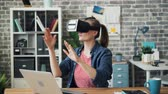 развлекать : Office worker in augmented reality glasses moving hands sitting at desk relaxing during break at work. Modern technology, gadgets and young people concept.