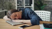 tembellik : Exhausted young lady is sleeping on laptop at work resting after hard day relaxing on workplace. Tired millennials, hard-working youth and business concept.