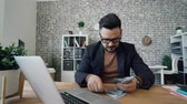 dollar : Rich entrepreneur handsome brunet in glasses is counting money smiling sitting at office table at work. Finance, wealthy people and salary concept. Stock Footage