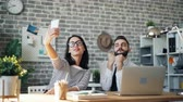 équipe de travail : Man and woman colleagues are taking selfie with smartphone camera sitting at desk in office posing smiling having fun. Youth, millennials and gadgets concept. Vidéos Libres De Droits