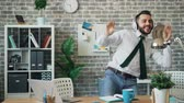 игривый : Cheerful office worker is listening to music in headphones dancing in workplace having fun alone. Happy young people, modern job and entertainment concept.