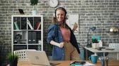 игривый : Crazy entrepreneur attractive girl is dancing in office listening to music through headphones having fun enjoying work break. Youth and modern gadgets concept. Стоковые видеозаписи
