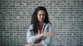schaam : Portrait of displeased young woman with long curly hair showing thumbs-down gesture on brick wall background. Dislike sign, people and attitude concept.