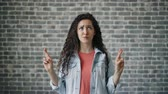 hurafe : Portrait of scared girl making praying hands gesture speaking standing alone on brick wall background. Hope for the best, people and human belief concept.
