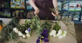 virágárus : Slow motion of female florist young woman in apron holding beautiful flowers making bouquet working in shop. Small business, profession and plants concept.
