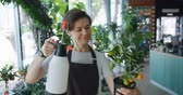 postřikovačů : Pretty young lady florist in apron is watering exotic plant in pot holding sprinkler smiling at work doing casual routine job. People and profession concept.
