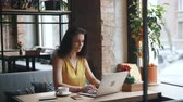 portátil : Good-looking girl student is working with laptop computer in cafe typing looking at screen smiling enjoying remote work. Happy youth and gadgets concept. Stock Footage