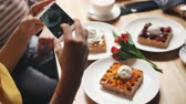 fotografando : Cafe customer girl is taking pictures of tasty food using smartphone camera touching screen using modern device. Lifestyle, dining out and youth concept. Stock Footage