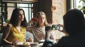 forchetta : Carefree women posing for smartphone camera in cafe holding flower smiling having fun enjoying meeting with friends and modern technology. Youth lifestyle concept.