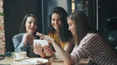 swiping : Joyful girls happy friends are looking at smartphone screen swiping smiling having fun in cafe enjoying media content. Modern technology and friendship concept.