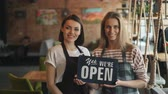 accogliente : Portrait of happy girls waitresses in aprons holding we are open sign standing in cozy cafe smiling looking at camera. Modern business and people concept.