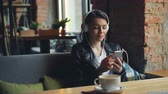 pausa pranzo : Young woman in headphones is listening to music using smartphone in modern cafe sitting at table relaxing enjoying favorite song. Happiness and hobby concept. Filmati Stock