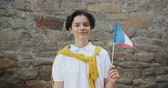 вентилятор : Portrait of joyful French teenager holding national flag of France smiling outdoors standing in the street alone looking at camera. People and patriotism concept. Стоковые видеозаписи