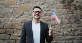 вентилятор : Portrait of happy American man waving official US flag outdoors smiling looking at camera standing in the street with brick wall in background. People and tourists concept.