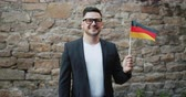 вентилятор : Slow motion portrait of smiling German man with national flag of Germany looking at camera standing outdoors in the city street. People, tourism and patriots concept. Стоковые видеозаписи