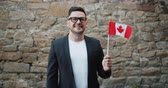 citoyenneté : Portrait of handsome bearded guy waving Canadian flag standing outdoors alone looking at camera and smiling. Patriotism, people and nationality concept.
