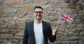 вентилятор : Portrait of good-looking Englishman with flag of the United Kingdom standing outdoors alone looking at camera and smiling. People and tourism concept. Стоковые видеозаписи
