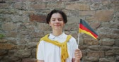 вентилятор : Slow motion portrait of German young boy waving flag of Germany smiling looking at camera standing outdoors with brick wall in background. People and tourism concept. Стоковые видеозаписи