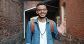 middle eastern ethnicity : Portrait of friendly cheerful Arabian man in stylish clothing waving hand outdoors smiling looking at camera. Hand gestures, people and greeting concept. Stock Footage