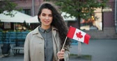 вентилятор : Portrait of pretty young lady patriot holding Canadian flag in the street smiling looking at camera on windy day. Beautiful people and nationality concept.