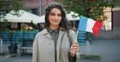 immigratie : Portrait of attractive female student standing outside with French national flag smiling looking at camera on windy summer day. People and patriotism concept.