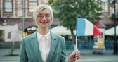 citoyenneté : Slow motion of happy French girl holding national flag smiling standing outdoors alone looking at camera feeling proud for country. Tourism and youth concept.