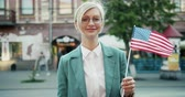 вентилятор : Portrait of pretty young blonde standing outdoors with American flag smiling looking at camera on windy day. Nationality, happy people and tourism concept. Стоковые видеозаписи