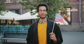 immigratie : Portrait of attractive African American student standing outdoors holding US flag looking at camera in the street on windy day. People and nationality concept.